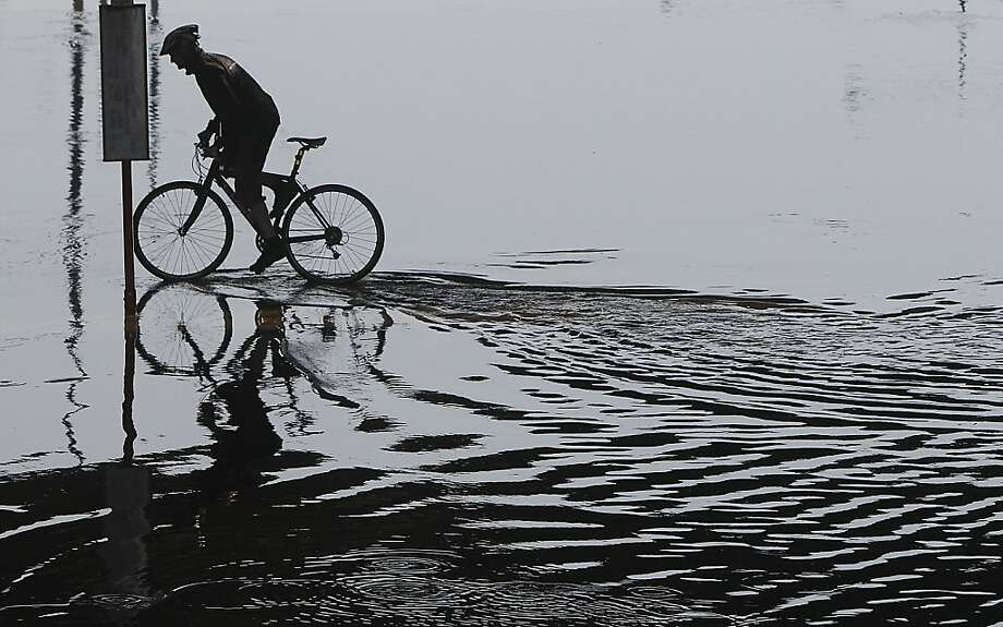 Rider in the rain:A cyclist pedals through floodwater after a downpour in Warsaw, Poland. Photo: Czarek Sokolowski, Associated Press