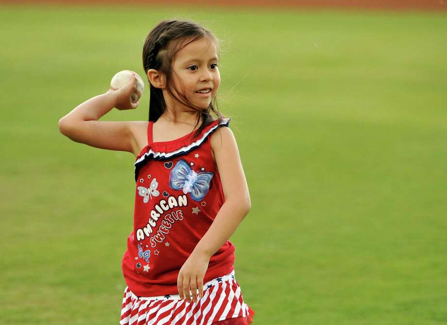 Five-year-old Hailey Sandoval throws the ceremonial first pitch before a Texas League baseball game between the Corpus Christi Hooks and the San Antonio Missions, Sunday, June 9, 2013, at Wolff Stadium in San Antonio. Hailey threw the pitch to her father, Army Staff Sgt. Alvino Sandoval, who surprised Hailey at the game with his return from active duty in Afghanistan. (Darren Abate/For the Express-News) Photo: San Antonio Express-News