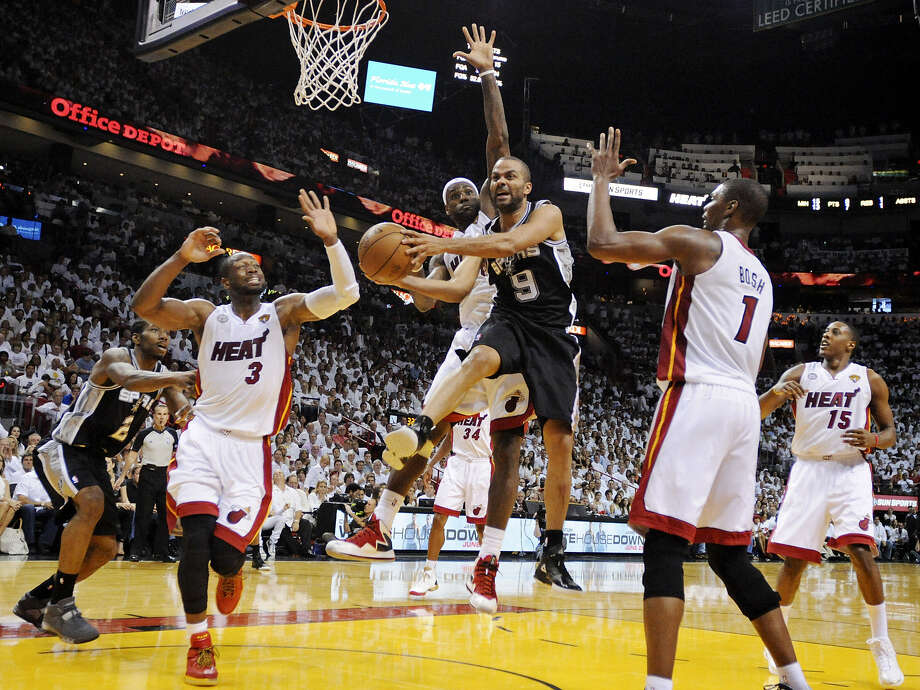 Tony Parker is surrounded under the basket by Miami's Dwyane Wade (left), LeBron James (center) and Chris Bosh. Parker had just 13 points and five turnovers. Photo: Photos By Edward A. Ornelas / San Antonio Express-News