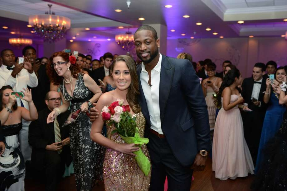 In this handout photo, Miami Heat player Dwyane Wade escorts Nicole Muxo to her senior prom at Archbishop Coleman Carroll High School on May 17, 2013 in Miami, Florida. Muxo invited Wade to accompany her to prom via YouTube. (Photo by Bobby Metelus/Getty Images)