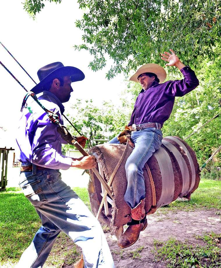 Seventeen year-old Hagen Brown, right, and works on his technique while his father John Brown, left, simulates bucking on their practice bull behind their Port Neches home on Friday, June 7, 2013. Photo taken: Randy Edwards/The Enterprise