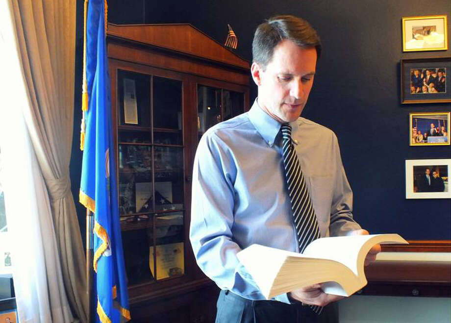 Rep. Jim Himes, D-Greenwich, peruses his office copy of the Dodd-Frank financial reform law that marks its third anniversary next month. Himes worked on the legislation after winning his House seat in 2008 and is now pushing for some amendments. Photo: Contributed Photo / Connecticut Post Contributed