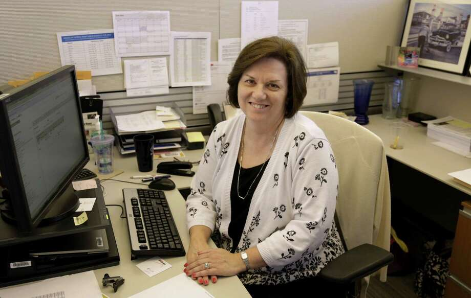 In this June 3, 2013, photo, Nora Kouba, an employee at USG Corporation sits at her work station in Chicago. Over the years, Kouba has made use of a benefit offered by USG that allows their workers to buy and sell vacation time, a perk that gives workers more flexibility in managing their time off. Photo: M. Spencer Green