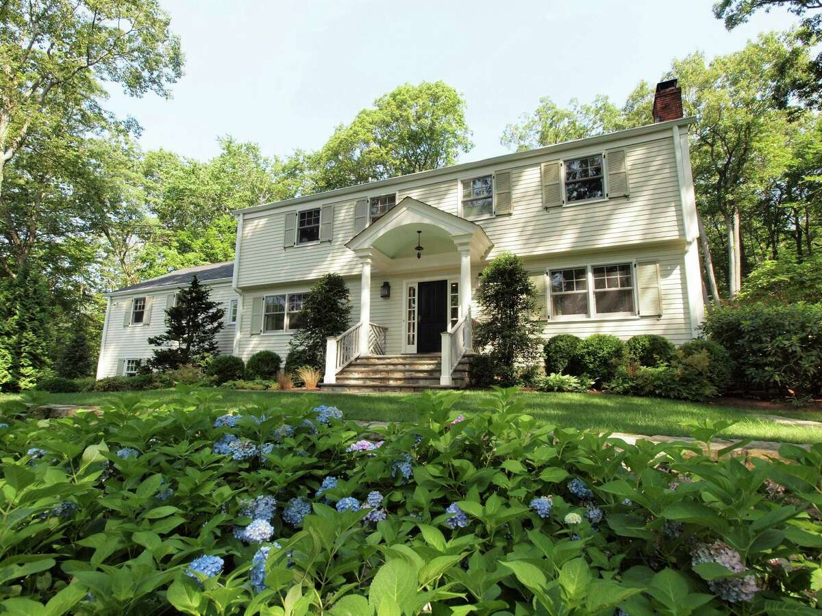The 11-room Colonial at 75 Glen Drive in New Canaan, on the market for $1,749,000, sits on a hill near the end of a private cul-de-sac and surrounded by perennial gardens.