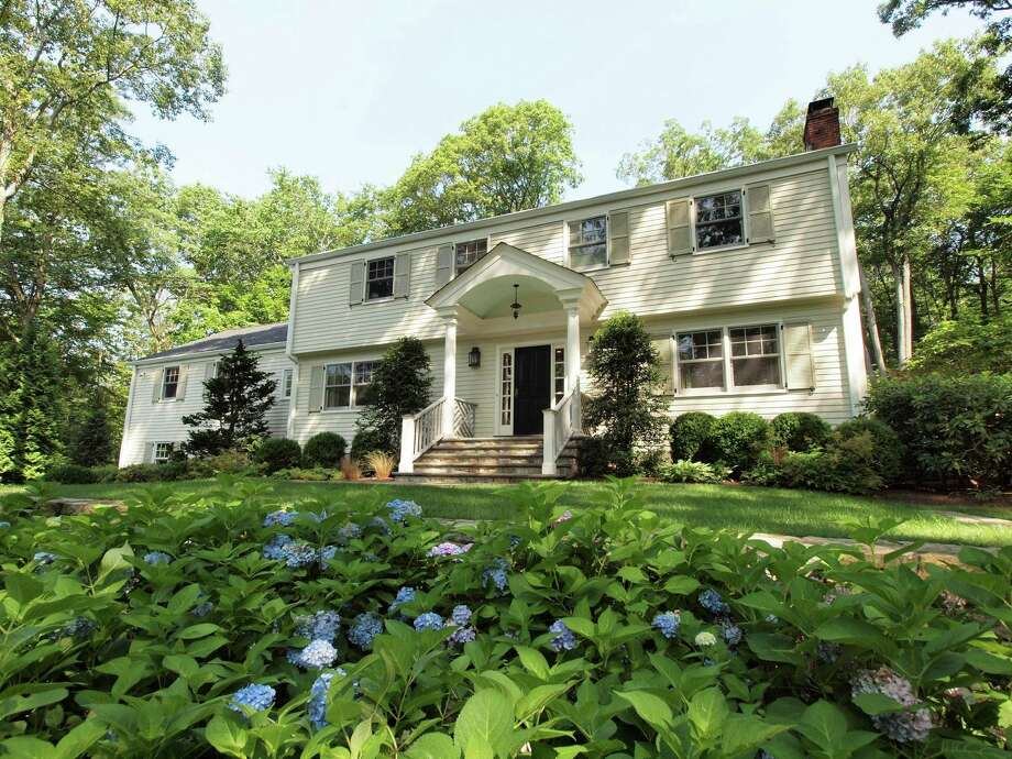 The 11-room Colonial at 75 Glen Drive in New Canaan, on the market for $1,749,000, sits on a hill near the end of a private cul-de-sac and surrounded by perennial gardens. Photo: Contributed