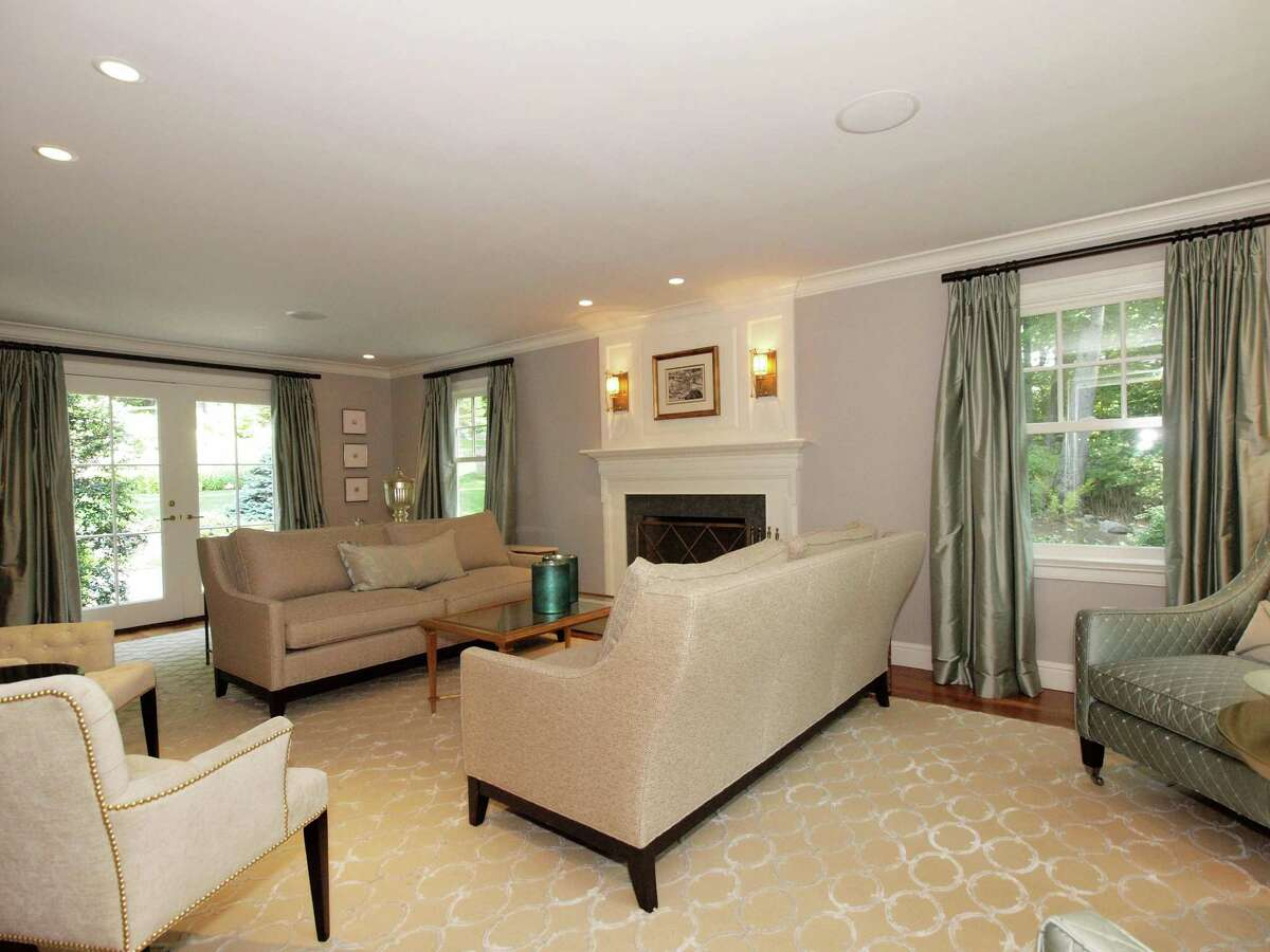 The formal living room at 75 Glen Drive in New Canaan includes French doors that give a first view out to the extensively redesigned back yard.
