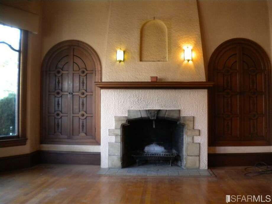 Interior of prop. #1: fireplace and living room. Photos via Redfin/MLS