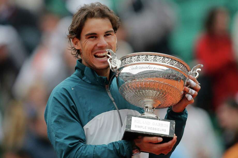 Spain's Rafael Nadal bites the trophy after winning against compatriot David Ferrer in three sets 6-3, 6-2, 6-3, in the final of the French Open tennis tournament, at Roland Garros stadium in Paris, Sunday June 9, 2013. Photo: Christophe Ena, AP / AP