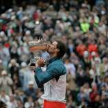 Spain's Rafael Nadal kisses the trophy after winning against compatriot David Ferrer in three sets 6-3, 6-2, 6-3, in the final of the French Open tennis tournament, at Roland Garros stadium in Paris, Sunday June 9, 2013.