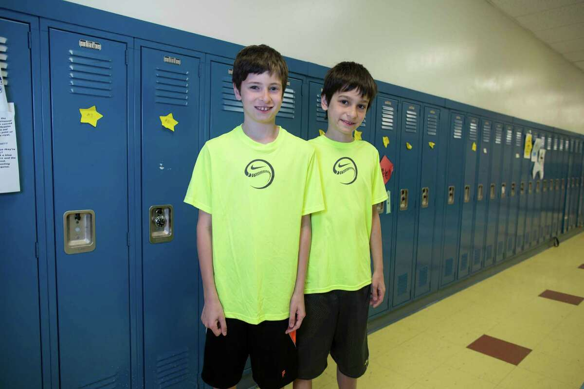In this Thursday, June 6, 2013 photo, Luke Rogers, left, and his twin brother, Sam, one of the twenty-four sets of twins from Highcrest Middle School in Wilmette, Ill. pose for a portrait at the school. The group is attempting to break a Guinness World record for the amount of twins in one grade which is currently 16 sets.
