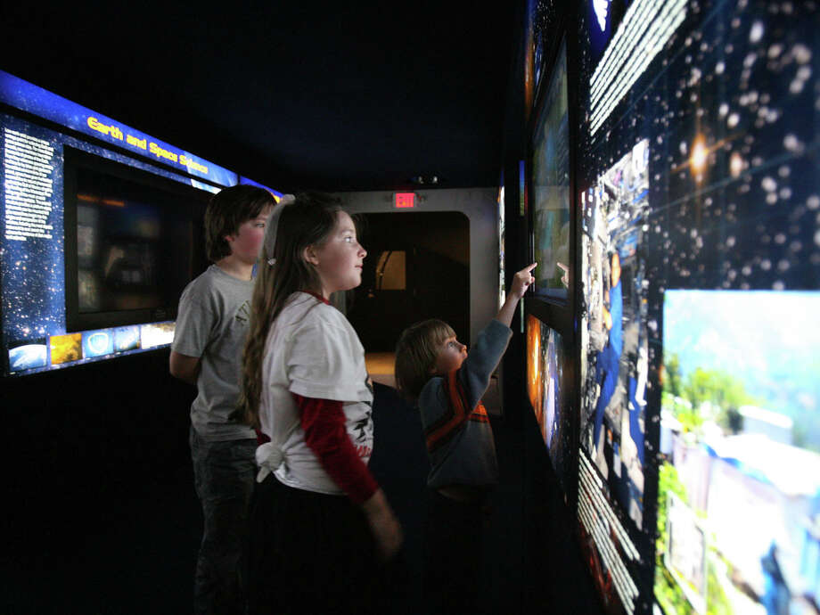 "Adam Champion, 5, interacts with a display while CJ Kisky, left, 10, and sister Annabelle Kisky, 8, look on during a preview of the ""Destination Station"" exhibit on Monday, June 10, 2013 at the Pacific Science Center, in Seattle. Photo: Aubrey Cohen,  Seattlepi.com"