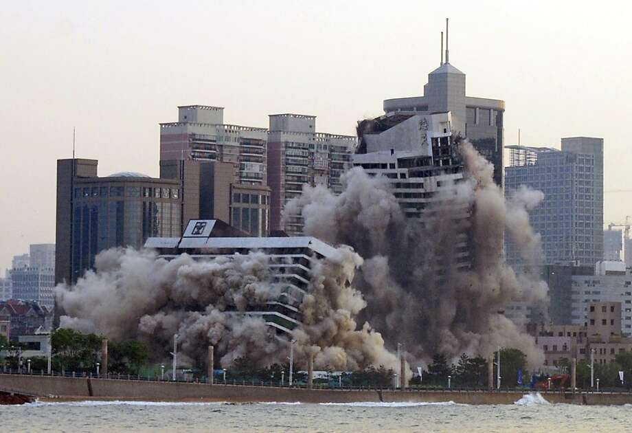 Dying young:Still in its 20s, a '80s-era five-star hotel comes tumbling down in a cloud of dust along  the waterfront in Qingdao, China. The building was demolished to make room for new  development. Photo: Associated Press