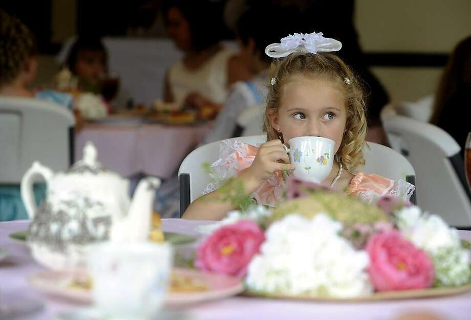 Contrary to popular opinion, the pinky is not pointed up: Seven-year-old Madison Cullifer practices her tea etiquette during Cape Fear Cotillion's Blueberry Belle tea party in Wilmington, N.C. Photo: Jeff Janowski, Associated Press
