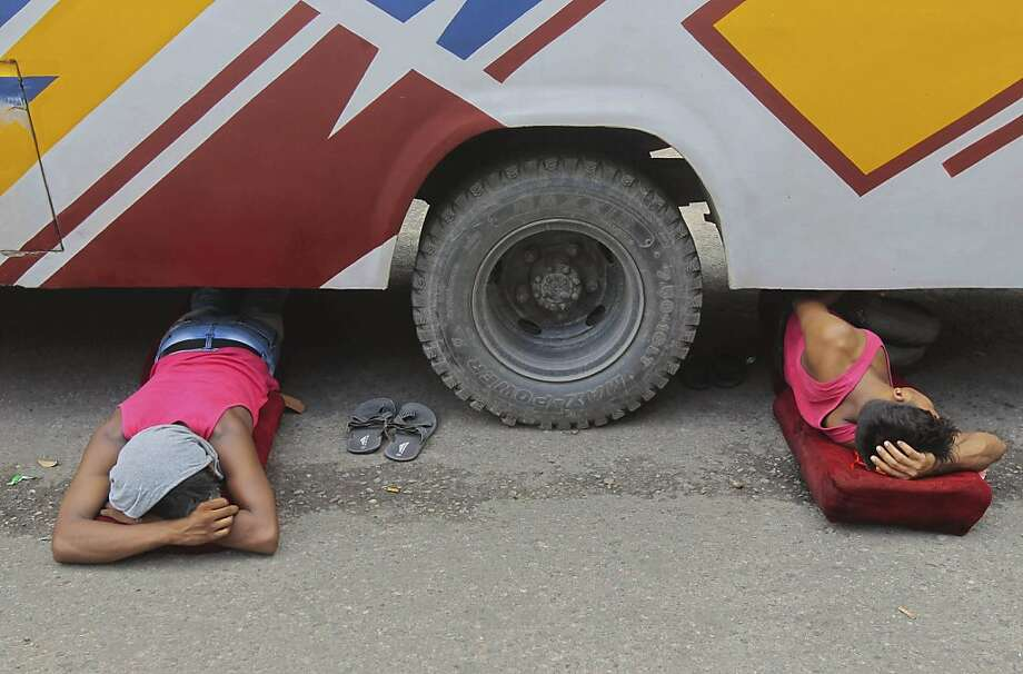 Questionable sleeping accommodations:Some men aren't thrown under the bus - they crawl under it voluntarily. (Dhaka, Bangladesh.) Photo: A.M. Ahad, Associated Press