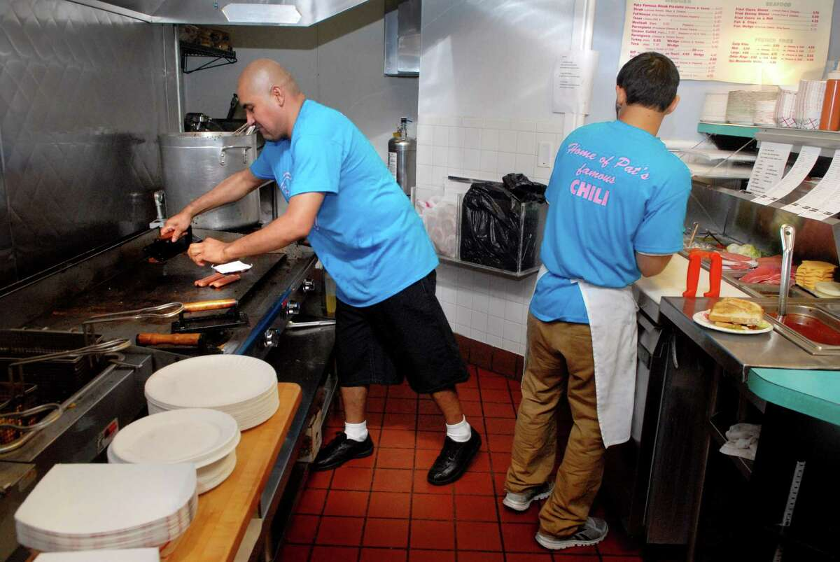 Chef Lucio campos and cook Miguel Enamorado work at Pat's Hubba Hubba restaurant in Stamford, Conn. on Monday June 10, 2013.