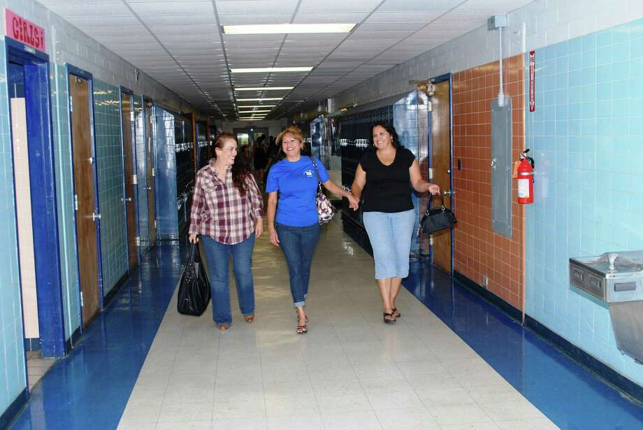 Left, South San Antonio High School alums Cynthia Casso (left), Idalia Rendon-Hagamon and Rose Rodriguez, take one last stroll down the school's first wing. Below, Two alumni from 1960 tour South San High School for one last time. Photo: Steve Valdez / For The Southside Reporter