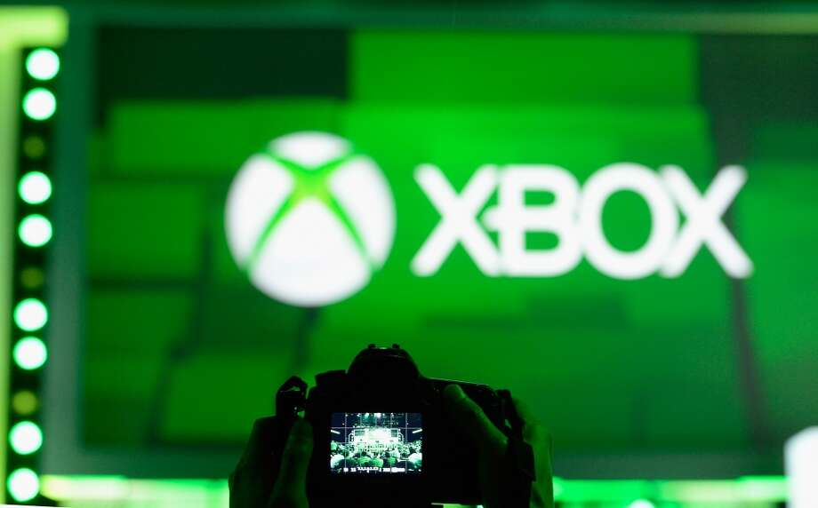 An attendee takes a photo of the XBOX logo during the Microsoft Xbox news conference at the Electronic Entertainment Expo at the Galen Center on June 10, 2013 in Los Angeles, California.