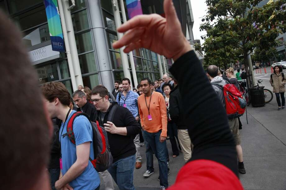 An Apple employee directs people people lined up at Moscone West as they enter the Apple Worldwide Developer's Conference on Monday, June 10, 2013 in San Francisco, Calif.
