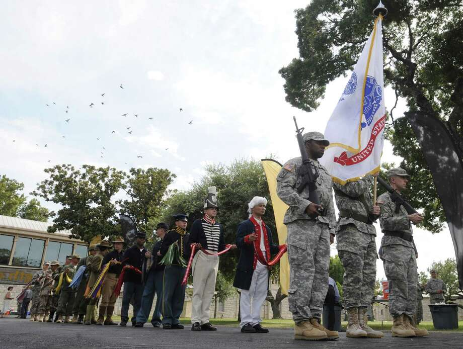 Soldiers carry the Army flag as others wear period uniforms  during a celebration of the Army's birthday and Flag Day last year. The Army will celebrate its 238th birthday on Friday. Photo: File Photo, San Antonio Express-News
