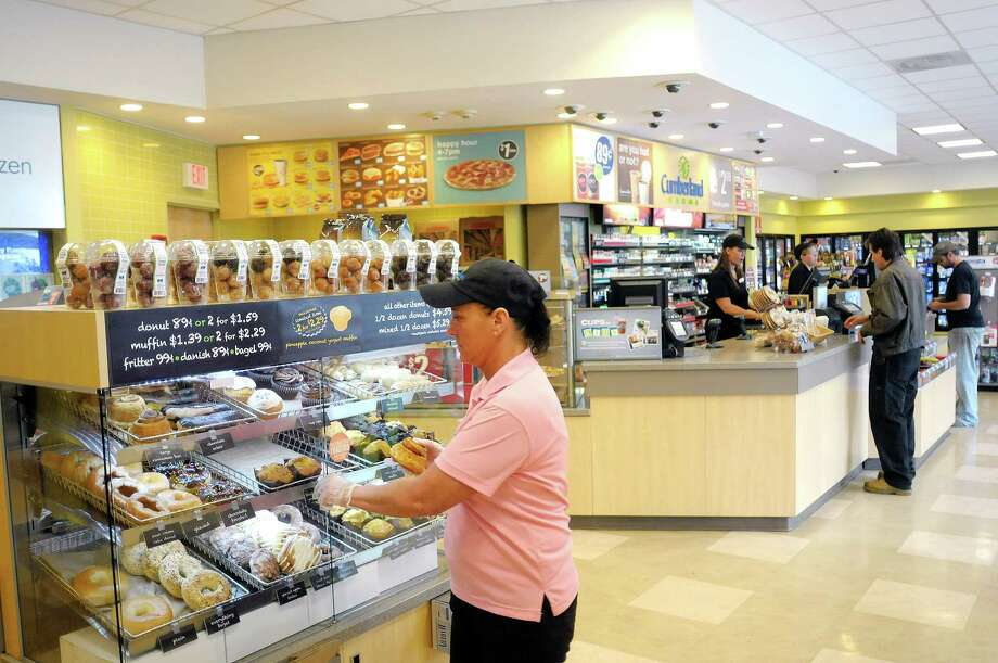Food service leader, Barbara Roberts, left, stocks the donuts at the Cumberland Farms store on Monday, June 10, 2013 in North Greenbush, NY.    (Paul Buckowski / Times Union) Photo: Paul Buckowski