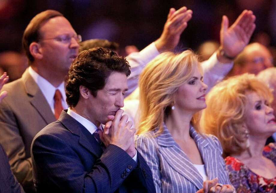 Lakewood Church Pastor Joel Osteen, left, stands next to his wife Victoria Osteen, who's the Church's Co-Pastor, as singers and the band perform on stage during his 11 a.m. service, Sunday, Aug. 28, 2011, in Houston. Olsteen's church averages about 40,000 people in attendance per week. ( Nick de la Torre / Houston Chronicle ) Photo: Nick De La Torre / © 2010 Houston Chronicle
