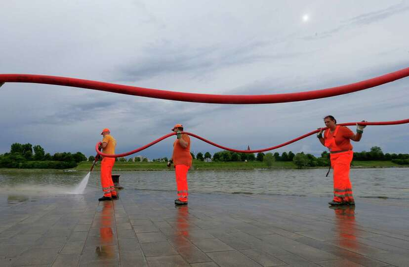 Street workers clean the shores of the Danube river with high pressure water after the flooding in V