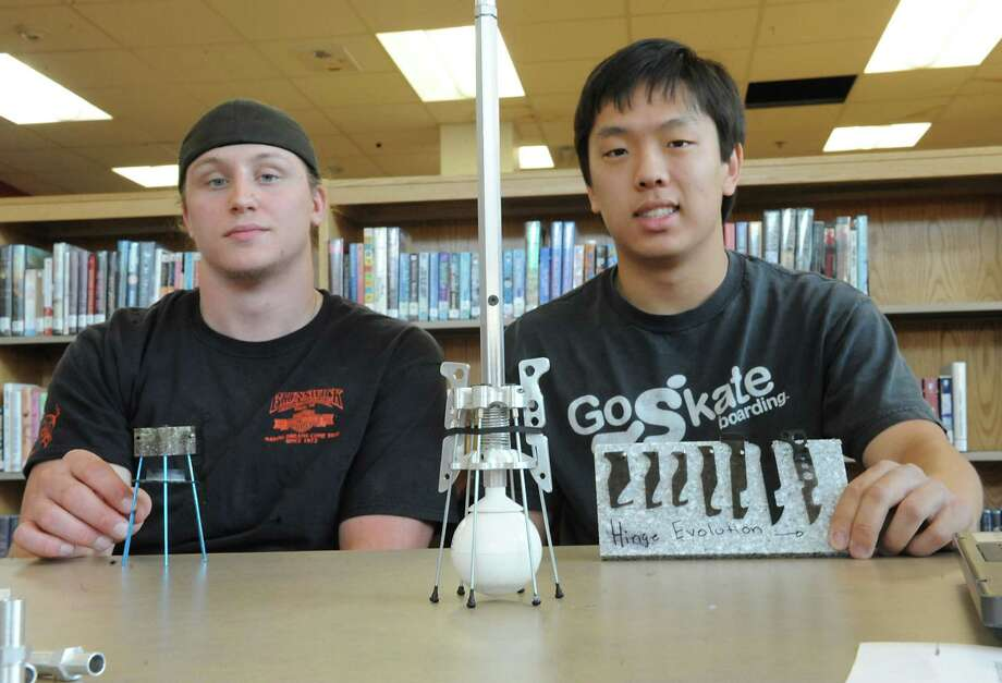 "From left, seniors Josh Sanzo, 17, and Gavin Dowse, 18, both of Niskayuna, sit with their invention ""C-Stand"" at Niskayuna High School on Monday, June 10, 2013 in Niskayuna, N.Y. Their invention makes it possible for people with a cane to stand the cane up next to them instead of leaning it against something and having it fall down. This year Niskayuna high school future engineers presented unique solutions to humanitarian problems.  (Lori Van Buren / Times Union) Photo: Lori Van Buren / 00022766A"
