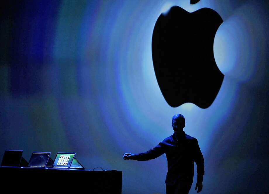 """Apple CEO Tim Cook reaches for an iPhone as he speaks at Apple's Worldwide Developers Conference. Apple said its next operating system, due out this fall, will include a """"kill switch"""" for mobile devices. Photo: Josh Edelson, AFP/Getty Images"""