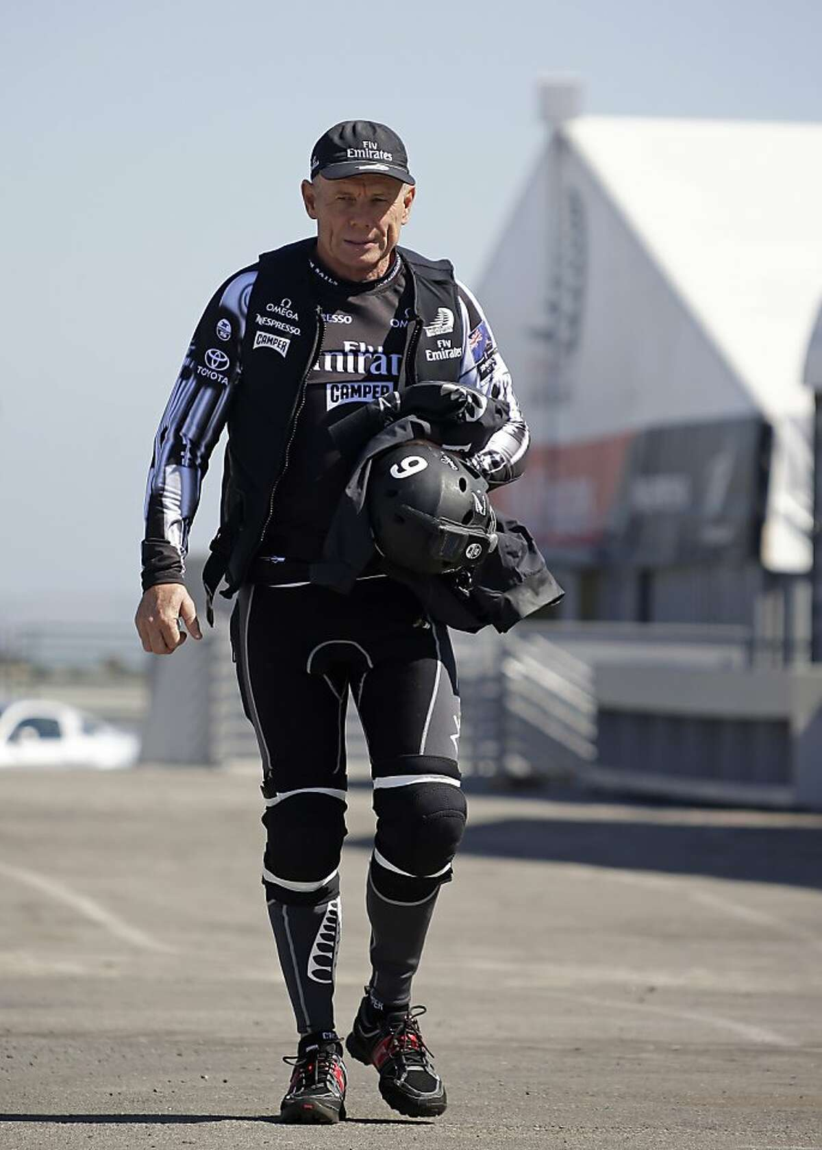 In this photo taken Friday May 24, 2013, Grant Dalton, the managing director of Emirates Team New Zealand, wears protective clothing and gear while heading out for a training run for the America's Cup in San Francisco. The margin for error is exceedingly small for an America's Cup sailor on the side of a tilting catamaran literally flying through the water at 40 mph. The days of gentlemen sailors in Sperry Topsiders and shorts grinding winches and pulling ropes are long gone, replaced by billionaire Larry Ellison's made-for-television, white-knuckle competition for fixed-sail yachts. (AP Photo/Eric Risberg)