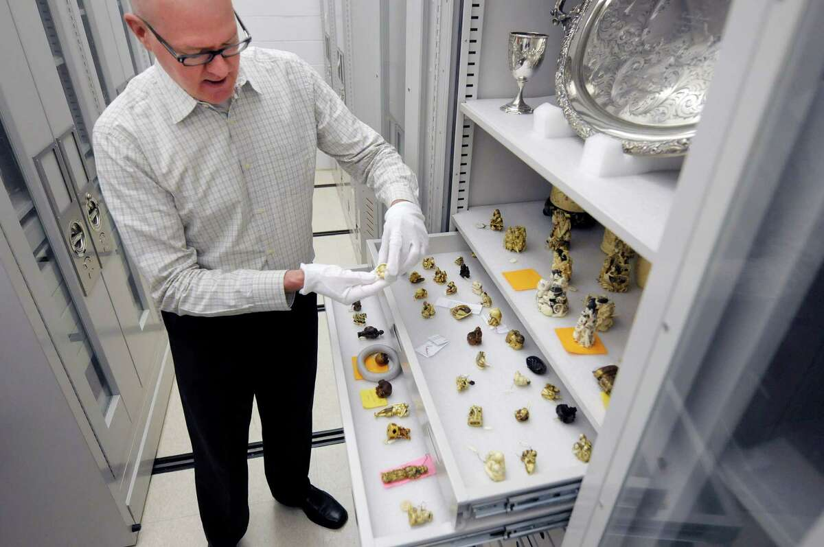 Doug McCombs, curator of history and material culture, icks up a netsuke carving in a collection's vault at the Albany Institute of History and Art on Monday, June 10, 2013 in Albany, NY. The netsuke carvings are carved out of bone, ivory, nuts and wood. The museum held a tour for members of the media to promote the launch of the museum's online catalog where items from the collection can be viewed online. (Paul Buckowski / Times Union)