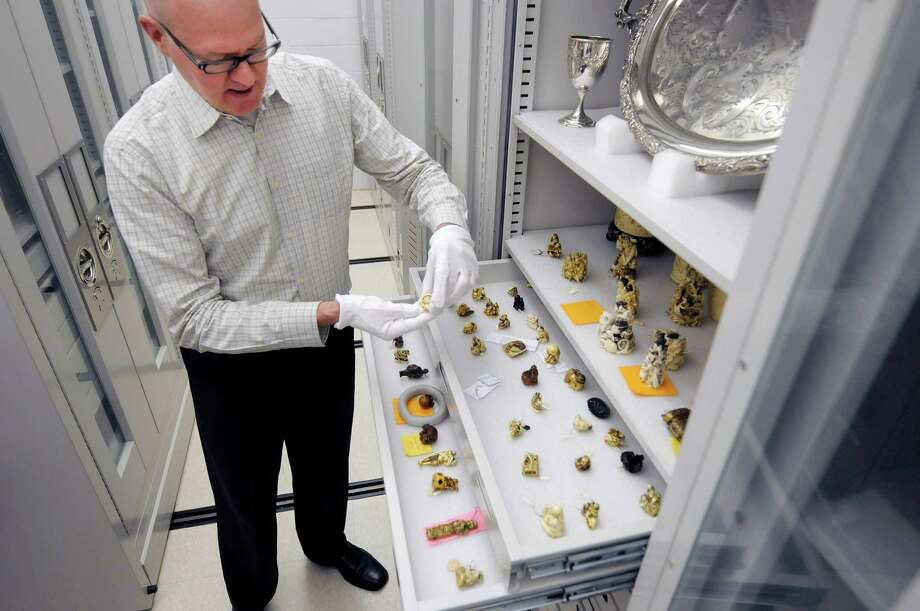Doug McCombs, curator of history and material culture, icks up a netsuke carving in a collection's vault at the  Albany Institute of History and Art on Monday, June 10, 2013 in Albany, NY.  The netsuke carvings are carved out of bone, ivory, nuts and wood.  The museum held a tour for members of the media to promote the launch of the museum's online catalog where items from the collection can be viewed online.    (Paul Buckowski / Times Union) Photo: Paul Buckowski