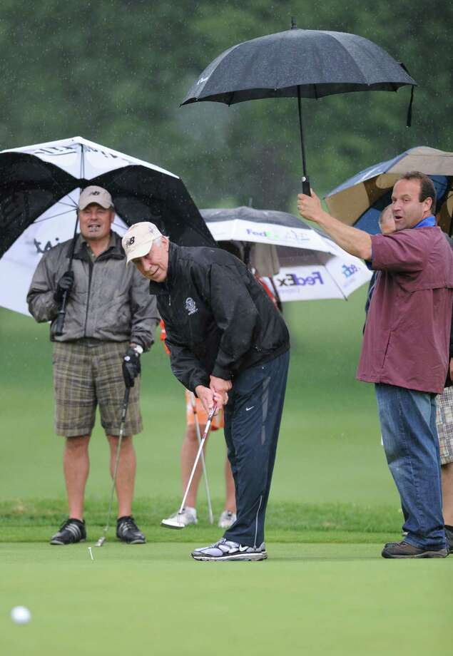 NFL Hall of Fame player Fred Biletnikoff putts as volunteer Mike Farber of Schenectady holds an umbrella in Hall of Fame Golf Classic tournament at Mohawk Country Club on Monday, June 10, 2013 in Schenectady, N.Y. The proceeds go toward the Ronald McDonald House Charities of the Capital Region, Inc. (Lori Van Buren / Times Union) Photo: Lori Van Buren / 00022761A