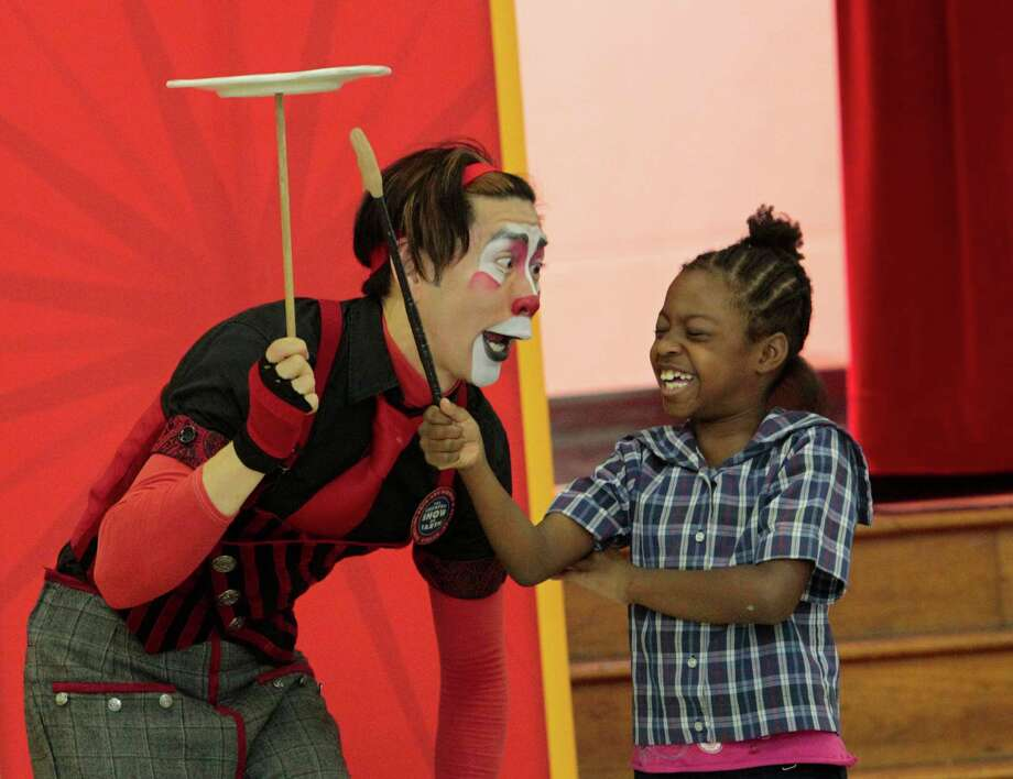 Rob Ringling shows seven year-old Nelah Kirkland how to balance a plate on stick Monday June 10, 2013. The clown performed for students at Yellowstone Academy in Houston, Texas in a special appearance that is part of the Summer Reading Program. The Ringling Bros Circus will be in Houston July 11-28th at Reliant Stadium. Photo: Billy Smith II, Chronicle / © 2013 Houston Chronicle
