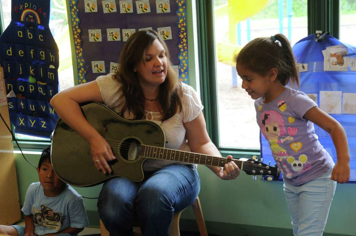 Teacher Stephanie Strazza sings with Jhayda Perez at Family Centers Head Start preschools at Armstrong Court in Greenwich, Conn., on Monday, June, 10, 2013.