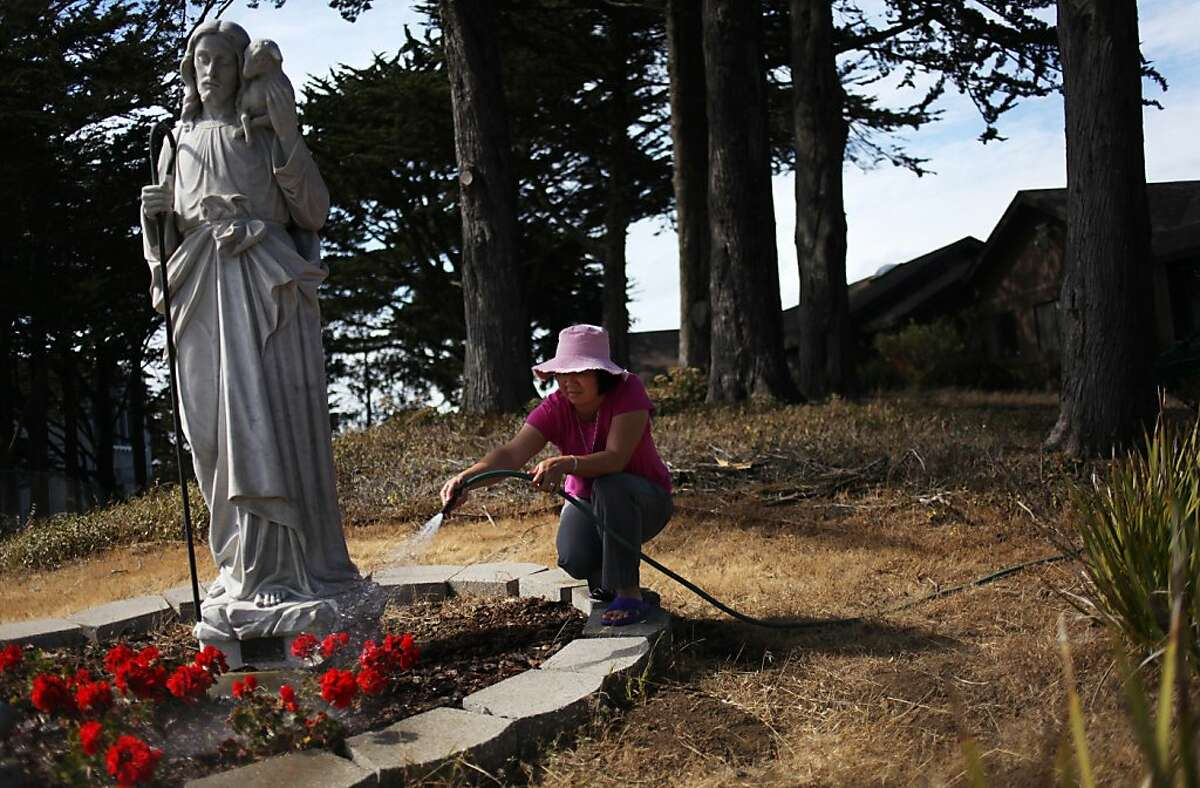 Sister Anna Tram Nguyen waters flowers in front of the Convent of the Good Shepherd on University Mound.