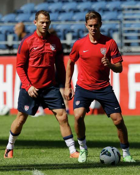 Dynamo players present and past - Brad Davis, left, and Stuart Holden - warm up for the U.S. national team's practice Monday ahead of tonight's World Cup qualifier against Panama at Seattle. Photo: Ted S. Warren, STF / AP
