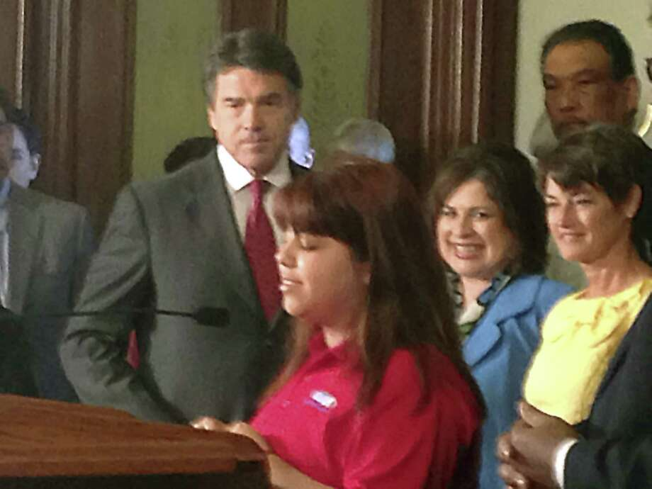 Cristina Salais introduces Gov. Rick Perry as he prepares to sign education reform bills into law. Salais is enrolled in the Alamo Colleges Information Technology Security Academy. Photo: Courtesy Of San Antonio Independent School District