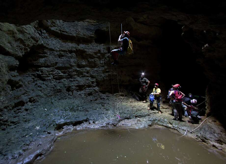 David Ochel starts a 75-foot climb to the surface from the middle level of the Seco Sinkhole in Medina County. A cave that's part of the Edwards Aquifer is another 75 feet down, accessible from behind the other cavers. Photo: William Luther / San Antonio Express-News
