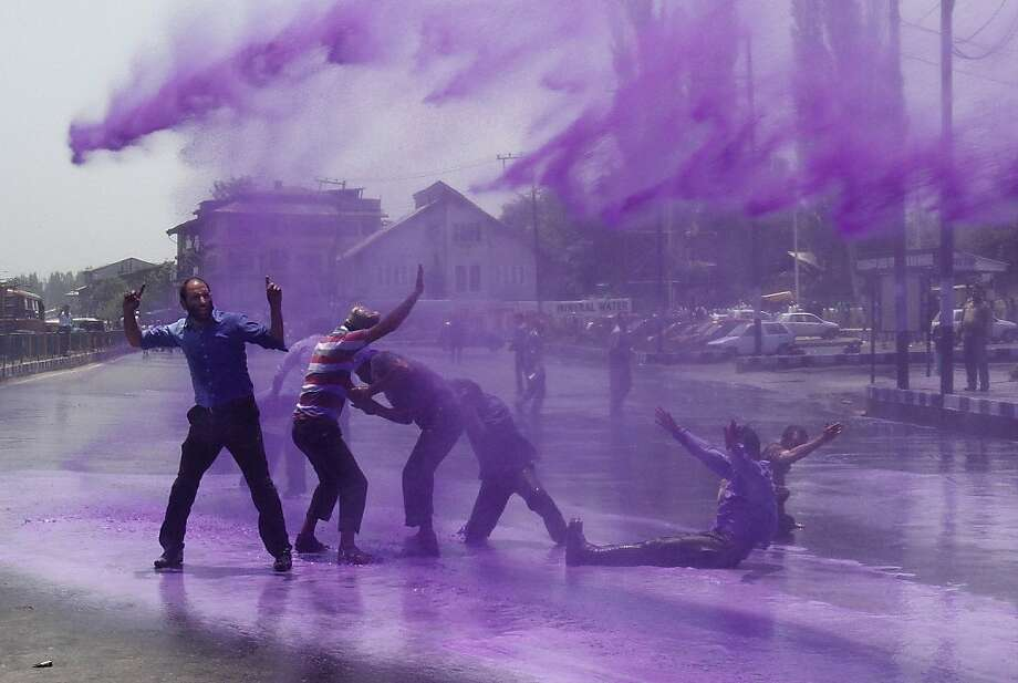 Policemen use colored water from a water cannon to disperse state government workers during a protest in Srinagar, India, Monday, June 10, 2013. The workers demanded regularization of contractual jobs and hike in salary. (AP Photo/ Mukhtar Khan) Photo: Mukhtar Khan, Associated Press