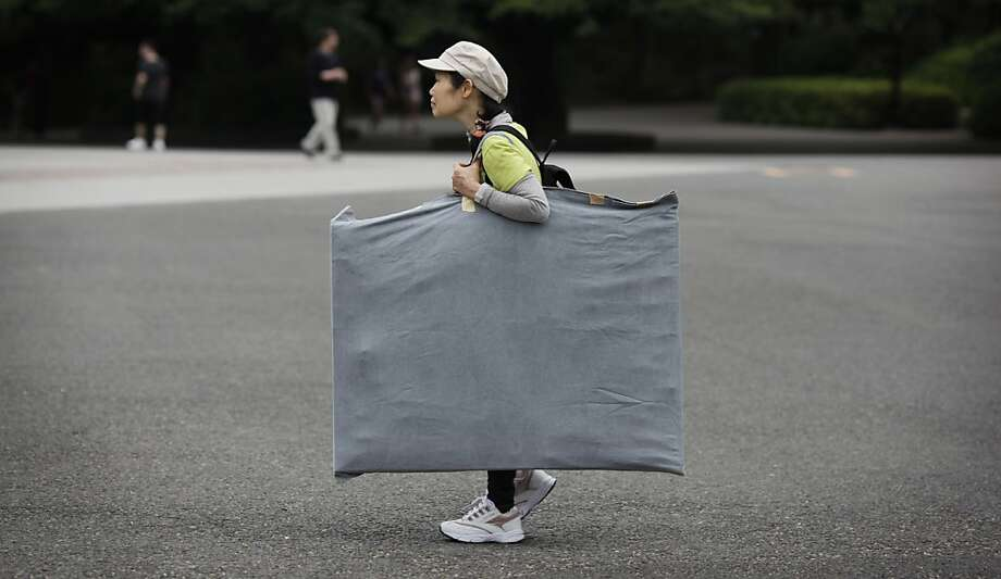 A woman carries a bag of painting canvas at Ueno park in Tokyo,  Monday, June 10, 2013. (AP Photo/Junji Kurokawa) Photo: Junji Kurokawa, Associated Press