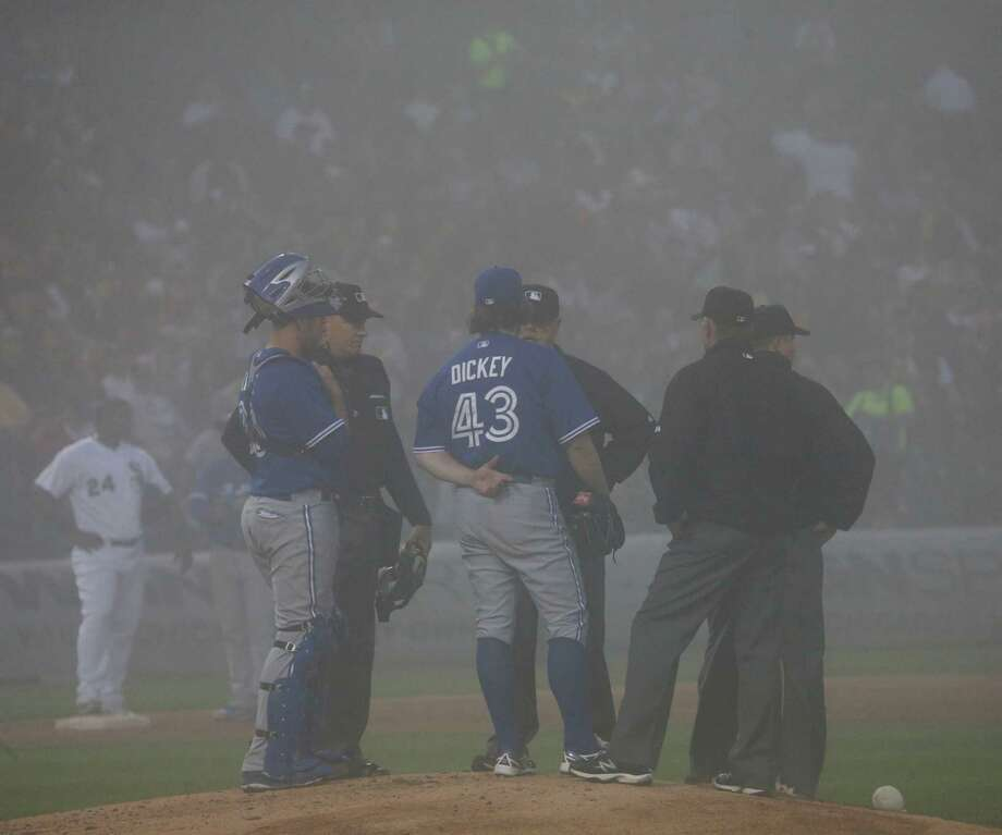 Toronto pitcher R.A. Dickey (43) and catcher Josh Thole confer with the umpires  just before a fog delay was called in the third inning of Monday night's game against the White Sox at Chicago. The game resumed 70 minutes later. Photo: Charles Rex Arbogast, STF / AP