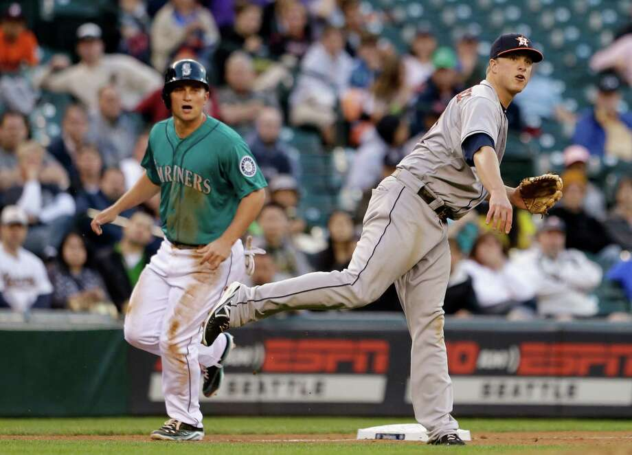 The Mariners' Kyle Seager, left, rounds third and watches the flight of Astros third baseman Matt Dominguez's throw to first in the fourth inning. Photo: Elaine Thompson, STF / AP