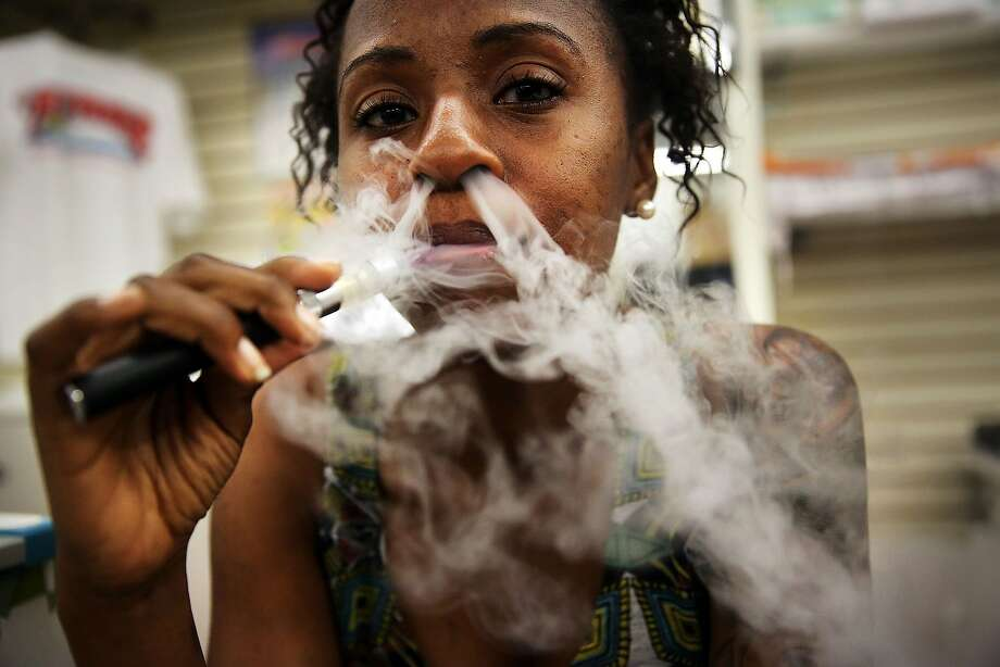 A safer smoke: Gabrielle Ortiz puffs an electronic cigarette at Vape New York in New York City. Electronic cigarettes, or e-cigarettes, are battery-powered devices that vaporize a nicotine-laced liquid solution into an aerosol mist, simulating the act of tobacco smoking without the carcinogenic fumes. Photo: Spencer Platt, Getty Images