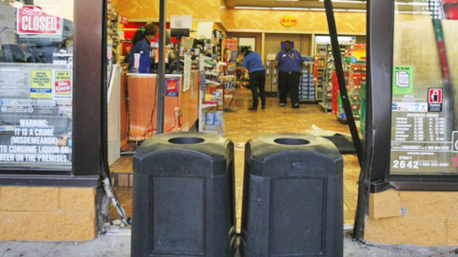 Workers clean up the mess after a smash-and-grab robbery Tuesday. Photo: (Cody Duty / Houston Chronicle)