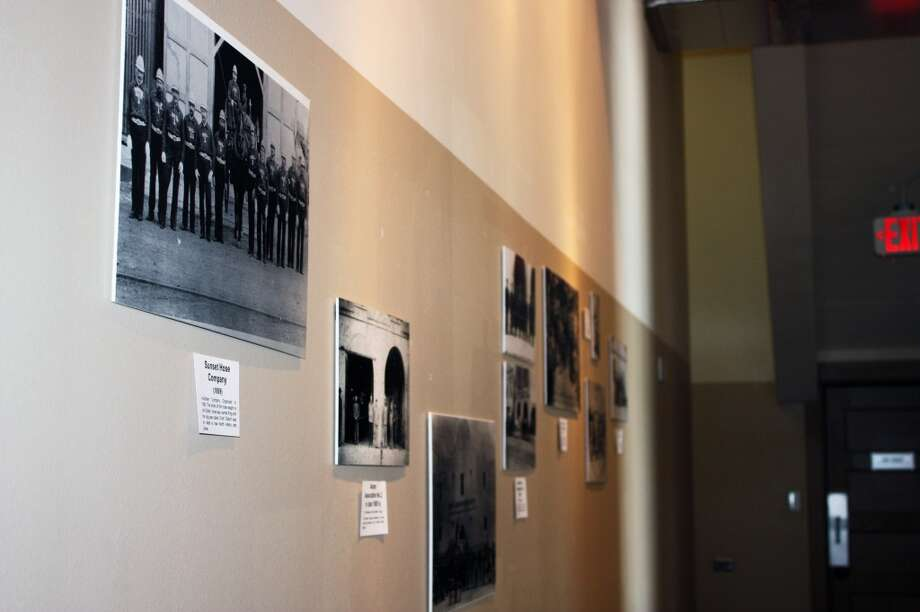 Immediately walking into the museum, the wall is decorated with pictures of firefighters from when the stations were staffed by volunteers. Photo: Emily Bamforth, Express-News