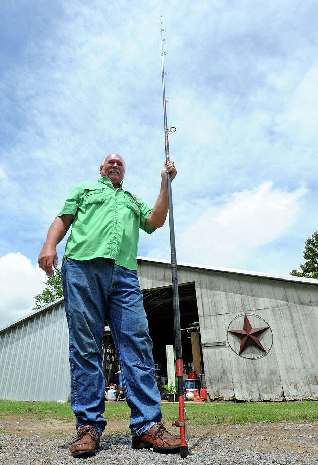 Lou McEachern stands Monday with the 13 foot eight inch fishing pole that he used to make a 700 foot cast over the Astrodome in January of 1991.  Photo taken Monday, June 10, 2013 Guiseppe Barranco/The Enterprise Photo: Guiseppe Barranco, STAFF PHOTOGRAPHER / The Beaumont Enterprise