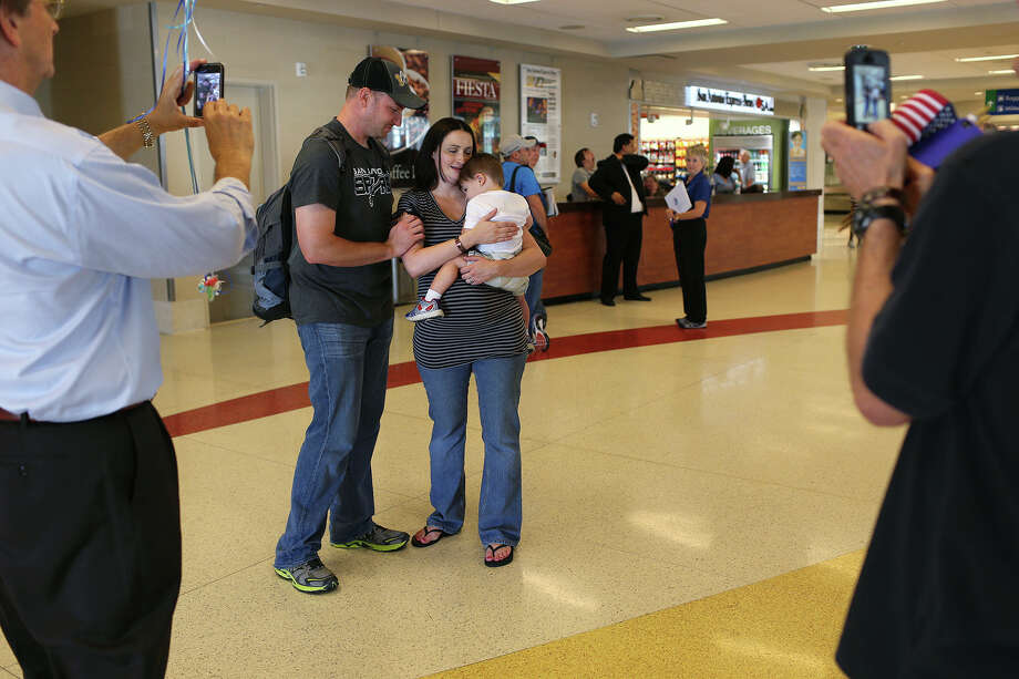 U.S. Army Spc. Corey Brandon, is greeted by his wife, Emily, and 18-month-old son, Hunter, as he arrives at the San Antonio International Airport, Sunday, June 9, 2013. Brandon was deployed to Afghanistan last September. He is hoping to score San Antonio Spurs playoff tickets for himself and his son. His father used to take him to Spurs games in his youth. His wife is pregnant with a due date of June 14. Photo: JERRY LARA, San Antonio Express-News / © 2013 San Antonio Express-News