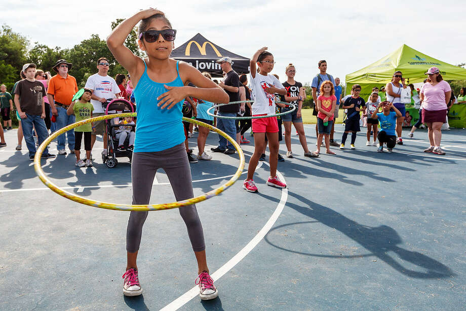 Sasami Cavan, 9 (left), and Lily Escobedo, 9, compete in the Hoola Hoop-Dee-Do in the San Antonio Sports' Fit Family Challenge event, Summer Fun Day, Saturday at Phil Hardberger Park. Photo: Photos By Marvin Pfeiffer / North Central News