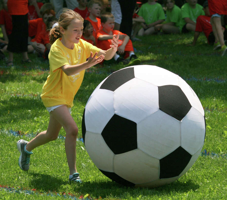 Second-grader Cassidy McKee speeds her giant soccer ball back to her teammates during Pear Tree Point School's annual Field Day. Photo: Contributed