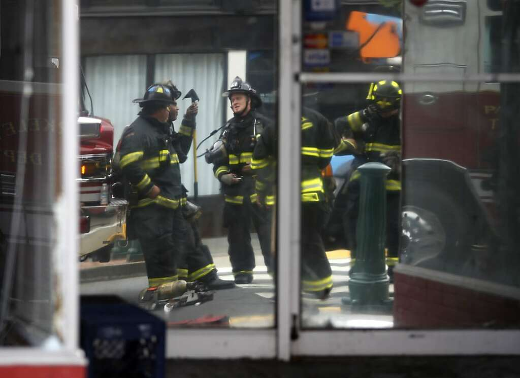 Firefighters Are Reflected In A Front Window After Battling Three Alarm Fire At The